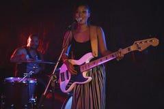 女性唱歌与男性鼓手在夜总会 库存照片