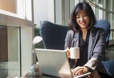 女性商人在计算机和饮用的咖啡上工作在办公室 免版税库存图片