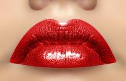 女性嘴特写镜头宏观射击  性感的与淫荡姿态的魅力红色嘴唇构成 洋红色光泽唇膏 库存照片