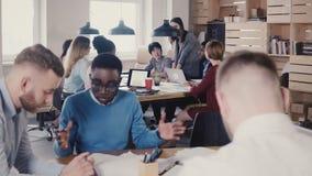 女性团队负责人给新的任务雇员 愉快的不同种族的同事由桌坐在遇见4K的办公室 股票视频