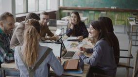 女性团队负责人给创造性的企业队带来文件 见面在现代办公室的混合的族种人 免版税库存照片