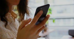 女性图表设计师谈话在手机在一个现代办公室4k 股票视频