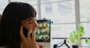 女性图表设计师谈话在手机在一个现代办公室4k 影视素材