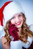 女性圣诞老人享受多雪的圣诞节的和蜂窝电话 免版税库存照片