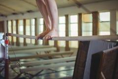 女性在单杠的体操运动员实践的体操 免版税库存照片