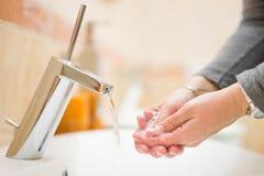 女性在卫生间里洗有自来水的手,浅dept 库存照片