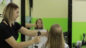 女性在客户` s头发的理发师喷洒的水 股票录像