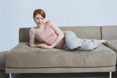 年轻女性在家说谎在沙发 库存照片