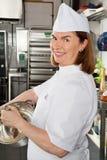 女性在容器的厨师混合的鸡蛋 免版税库存图片
