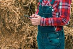 女性在手机的农夫键入的sms消息 免版税库存照片