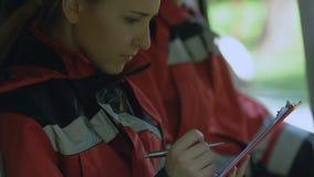 女性在救护车汽车的医务人员填装的纸,微笑对照相机,急救 股票视频