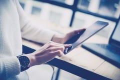 女性在数字式片剂的手感人的按钮特写镜头视图在木书桌 概念年轻商人使用 图库摄影