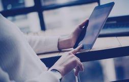 女性在数字式片剂的手感人的按钮特写镜头视图在木书桌 概念年轻商人使用 免版税图库摄影