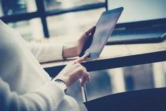 女性在数字式片剂的手感人的按钮特写镜头视图在木书桌 概念年轻商人使用 库存图片