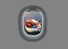 年轻女性在日落的一条木小船在平面窗口里 在飞机飞行地产海景视窗之上
