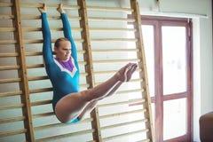 女性在木肋木的体操运动员实践的体操 免版税库存图片