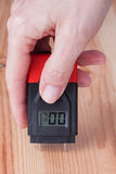 女性在木头的手测量的湿气 免版税库存照片