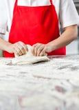 女性在杂乱柜台的厨师揉的面团 免版税库存照片