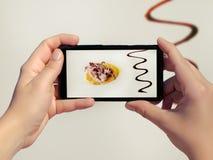 女性在白色背景的一家餐馆拍优质食物的照片在手机 优质烹调象章鱼  免版税库存图片
