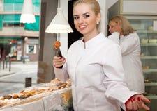 女性在糖果店的卖主提供的甜点 库存照片