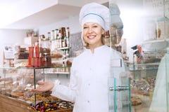女性在糖果店的卖主提供的甜点 图库摄影