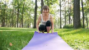 女性在绿草的健身教练员展开的瑜伽席子慢动作录影在公园 做体育锻炼和 影视素材