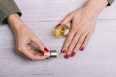 女性在钉子的手应用的油 库存照片