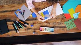 女性在飞溅纸拼贴画的雇员创造性的设计师图画放大在有坐在桌上的蜡笔的笔记本 股票录像