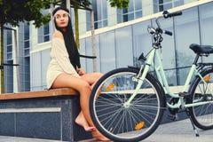 女性坐在现代大厦背景的一条长凳,在自行车乘驾后 免版税库存照片