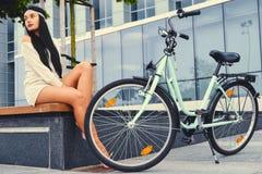 女性坐在现代大厦背景的一条长凳,在自行车乘驾后 图库摄影