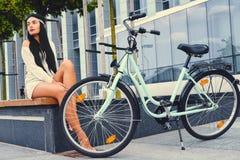 女性坐在现代大厦背景的一条长凳,在自行车乘驾后 库存图片