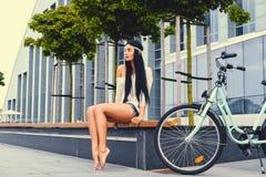 女性坐在现代大厦背景的一条长凳,在自行车乘驾后 库存照片