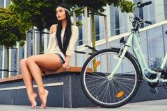 女性坐在现代大厦背景的一条长凳,在自行车乘驾后 免版税图库摄影