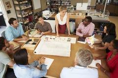 女性坐在表上的建筑师上司主导的会议  免版税库存照片
