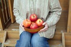 女性坐门廊并且拿着有苹果接近的碗 库存图片