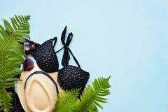 女性夏天比基尼泳装泳装和辅助部件拼贴画在蓝色与棕榈分支、帽子和太阳镜 库存照片