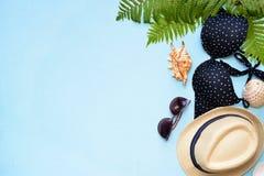 女性夏天比基尼泳装泳装和辅助部件拼贴画在蓝色与棕榈分支、帽子和太阳镜 库存图片