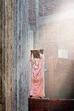 女性大厦工作者运载在她的头的一些瓦砾 免版税库存图片