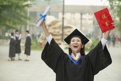 年轻女性大学毕业生,在与文凭的天空中举的胳膊 免版税库存图片