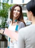女性大学生为她的朋友提供一本书 免版税库存图片