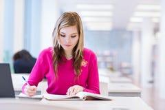 女性大学生在图书馆里 免版税图库摄影