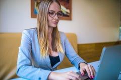 女性大学生有在网上学会通过手提电脑,坐在coworking的空间 库存图片