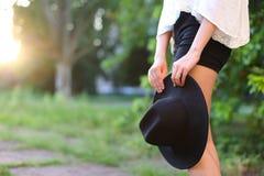 女性太阳腿的帽子可爱的日落图象 免版税库存图片