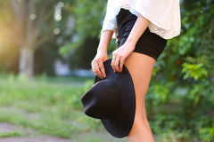 女性太阳腿的帽子可爱的日落图象 免版税图库摄影