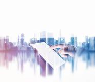 女性她的phablet手触摸屏,被弄脏的城市背景 两次曝光 免版税库存照片