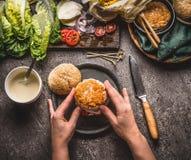 女性妇女递做与鸡的自创鲜美汉堡在与成份的土气厨房用桌背景 免版税库存图片