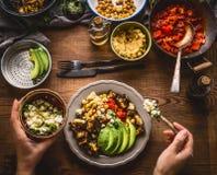 女性妇女递在碗的供应的健康素食膳食用鹰嘴豆纯汁浓汤,烤菜,红色辣椒粉蕃茄炖煮的食物, a 免版税库存图片
