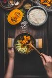 女性妇女递拿着罐和匙子和烹调在黑暗的土气厨房用桌与成份,顶视图上的南瓜意大利煨饭 clea 库存照片