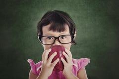 女性学龄前儿童吃红色苹果 免版税库存照片