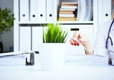 女性实习生或医生在办公室递搜寻耐心` s纪录 在医疗的行政工作 库存图片